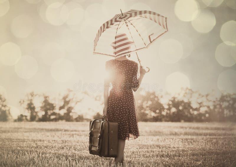 Junge Frau mit Regenschirm und Koffer stockfotografie