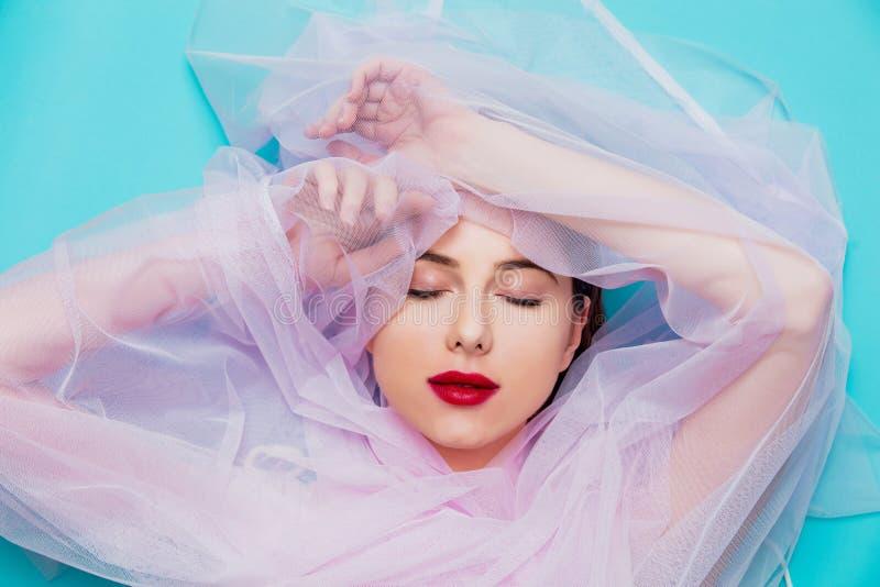 Junge Frau mit rosa Tulle auf blauem Hintergrund stockfotos