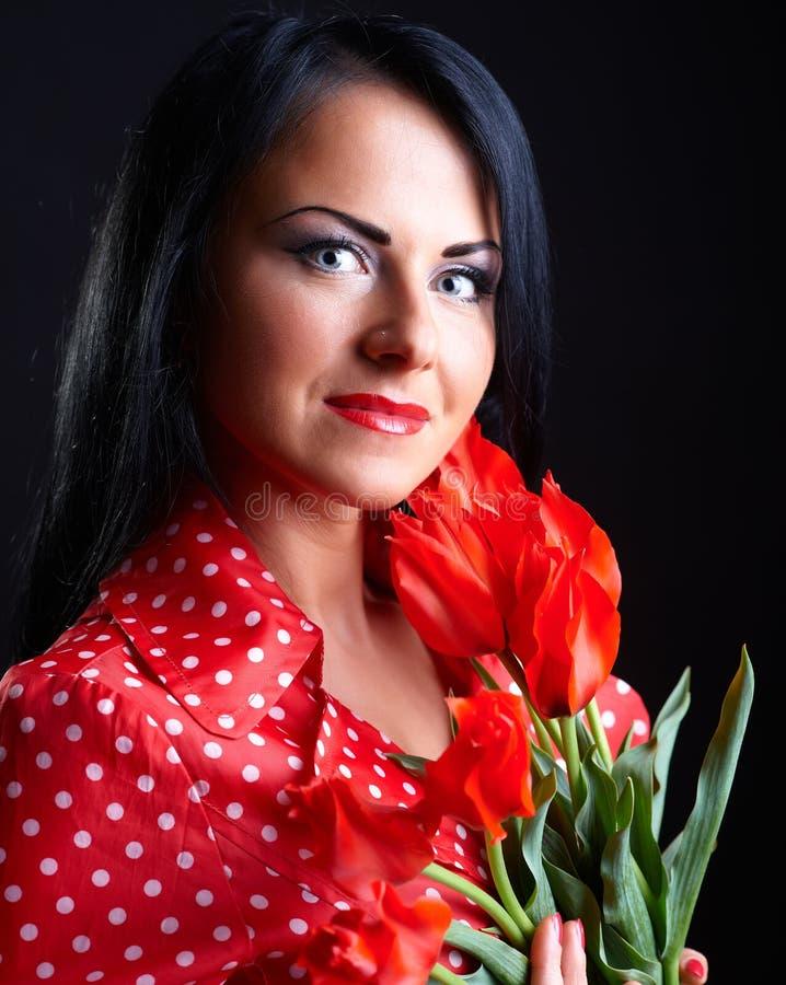 Junge Frau mit roten Blumen lizenzfreies stockbild