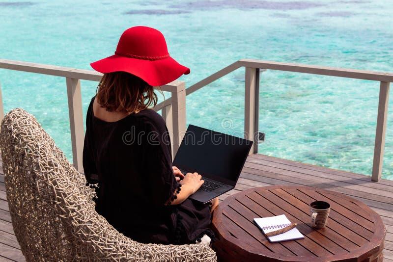 Junge Frau mit roter Hutfunktion auf einem Computer in einem tropischen Bestimmungsort stockfoto