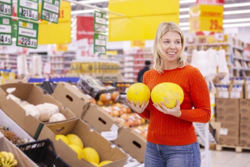 Junge Frau mit saftigen Melonen im Supermarkt stockbilder