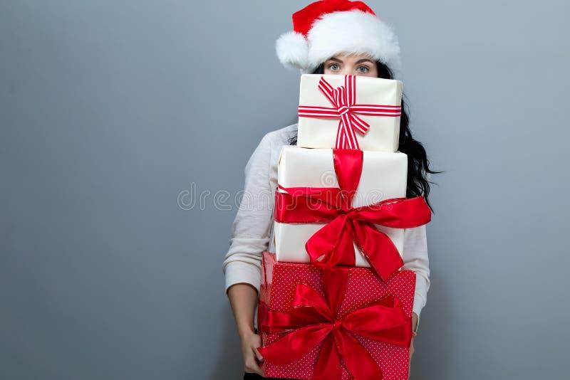 Junge Frau mit Sankt-Hut, der Geschenkboxen hält lizenzfreies stockfoto