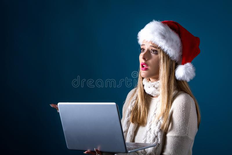 Junge Frau mit Sankt-Hut unter Verwendung ihres Laptops stockfoto