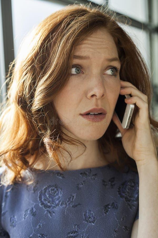 Junge Frau mit schönen blauen Augen sprechend am Handy lizenzfreie stockfotografie