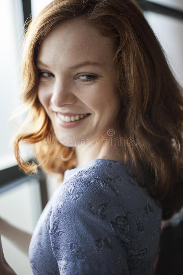 Junge Frau mit schönen blauen Augen und dem roten Haar stockfotografie