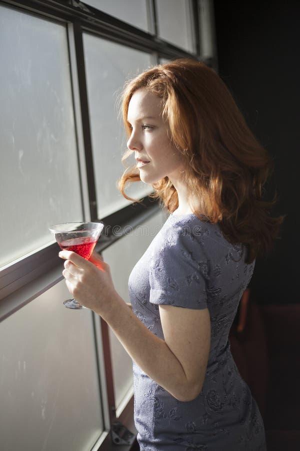 Junge Frau mit schönen blauen Augen und dem roten Haar ein Rot trinkend lizenzfreie stockfotografie
