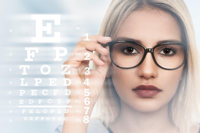 Junge Frau mit Schauspielen auf Sehvermögentestseitehintergrund lizenzfreies stockbild