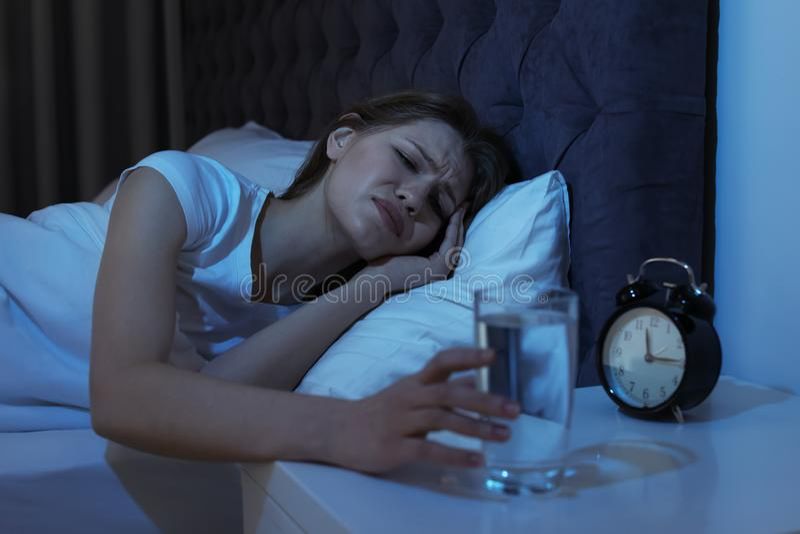 Junge Frau mit schrecklichen Kopfschmerzen nachts Glas nehmend lizenzfreie stockbilder