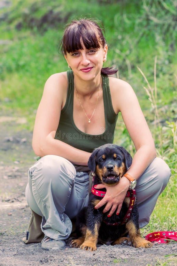Junge Frau mit seinem Rottweiler-Welpen lizenzfreie stockfotos