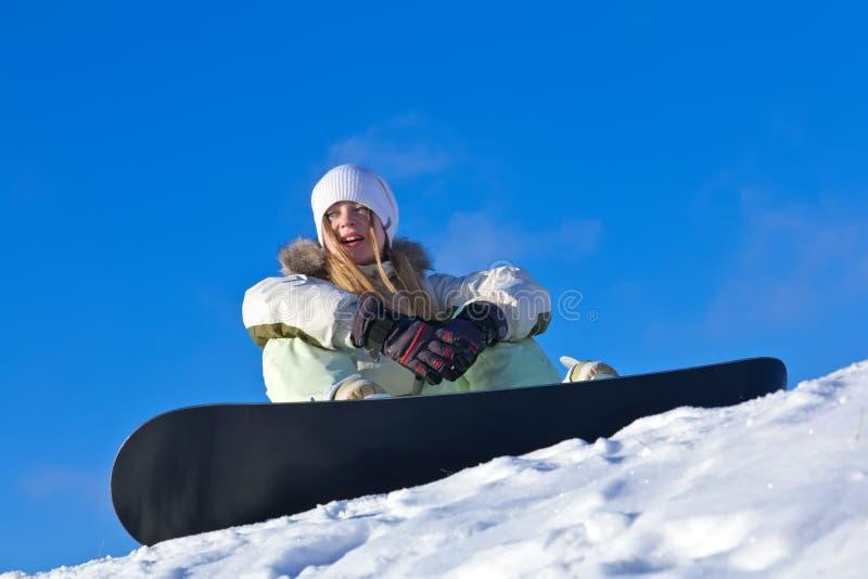 Junge Frau mit Snowboard auf einer Steigung lizenzfreie stockfotos