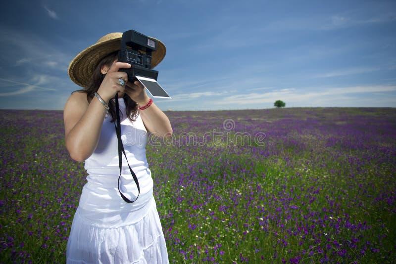 Junge Frau mit sofortiger Fotokamera lizenzfreie stockbilder