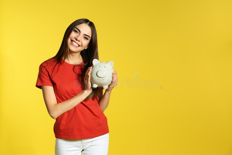 Junge Frau mit Sparschwein auf Farbhintergrund Geldeinsparung lizenzfreies stockfoto