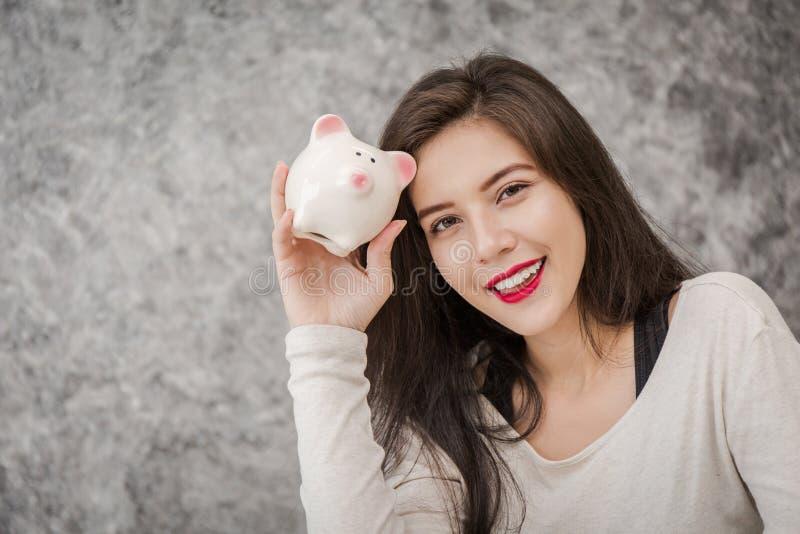 Junge Frau mit Sparschwein im Raum stockfotos