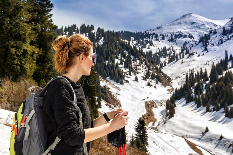 Junge Frau mit Spazierstöcken auf einem Hintergrund von Schnee-mit einer Kappe bedeckten Bergen lizenzfreies stockbild