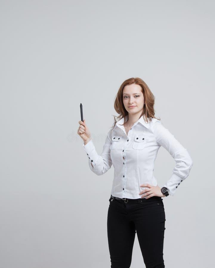 Junge Frau mit Stift auf grauem Hintergrund lizenzfreie stockbilder