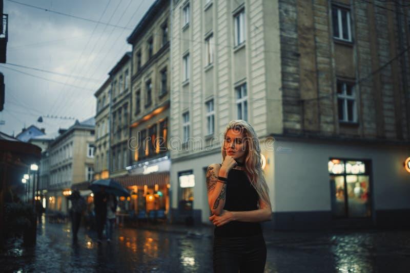 Junge Frau mit Tätowierung auf Kerzen auf Stadtstraße am Vorabend stockbild
