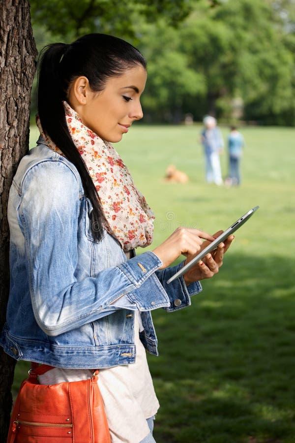 Junge Frau mit Tablette im Park stockfotos