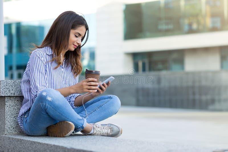 Junge Frau mit Telefon hörend Musik, sitzendes entspanntes im Freien mit Kopienraum lizenzfreies stockfoto