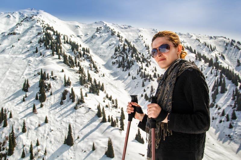 Junge Frau mit Trekking haftet auf dem Hintergrund von Bergspitzen lizenzfreie stockbilder