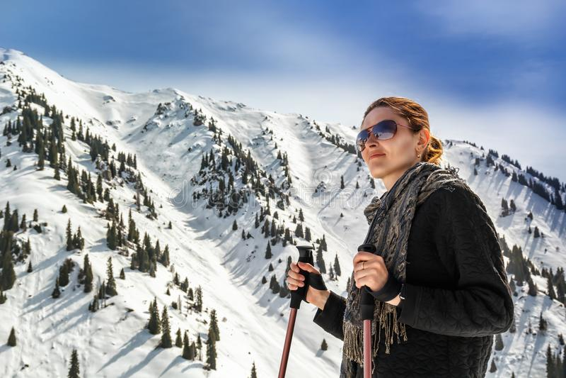 Junge Frau mit Trekking haftet auf dem Hintergrund von Bergspitzen stockfotos