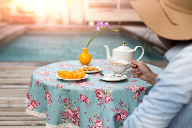 Junge Frau mit trinkendem Tee des Hutes mit Keks und orange Frucht lizenzfreies stockbild