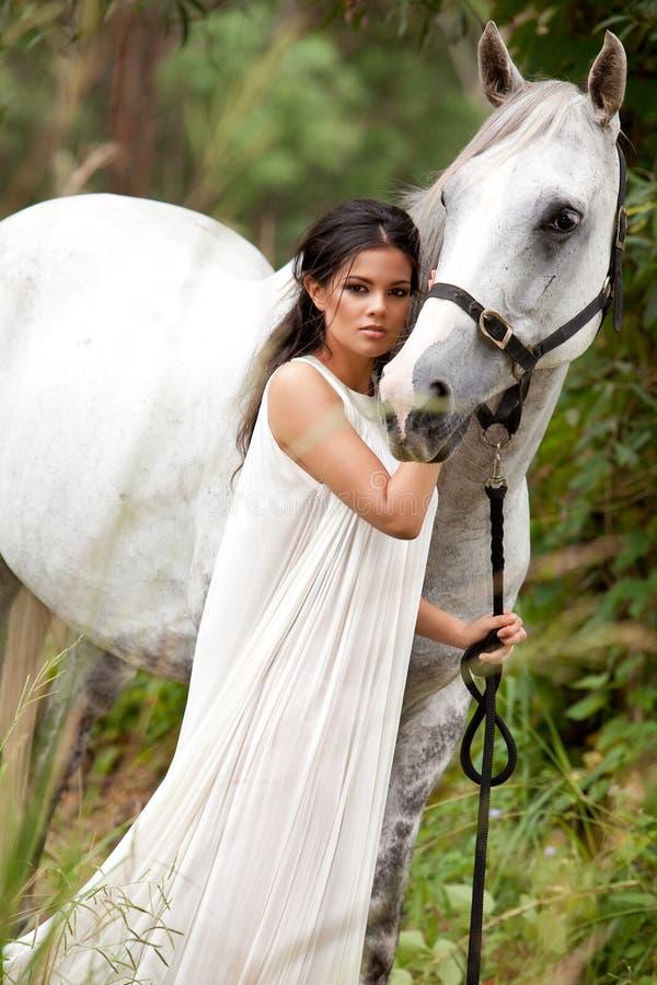 Junge Frau mit weißem Pferd lizenzfreies stockfoto