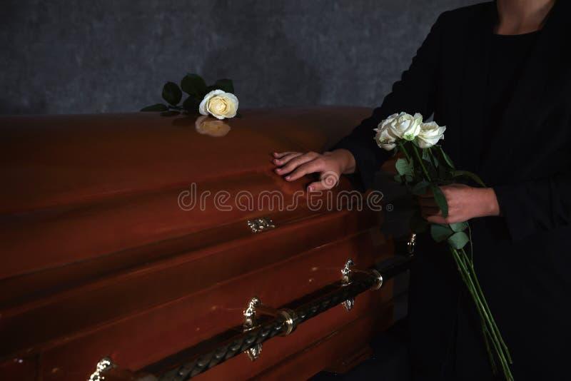 Junge Frau mit weißen Rosen nahe Schatulle im Beerdigungsinstitut stockfoto