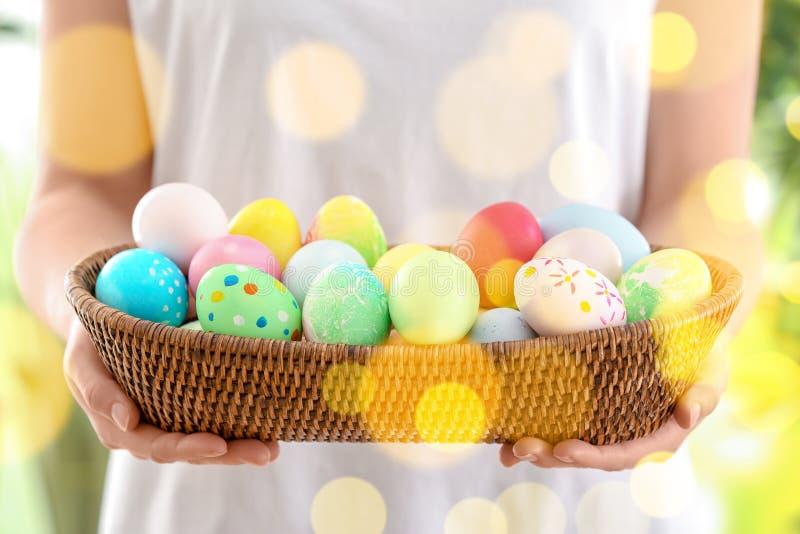 Junge Frau mit Weidenschüssel voll bunten Ostereiern, Nahaufnahme stockbilder