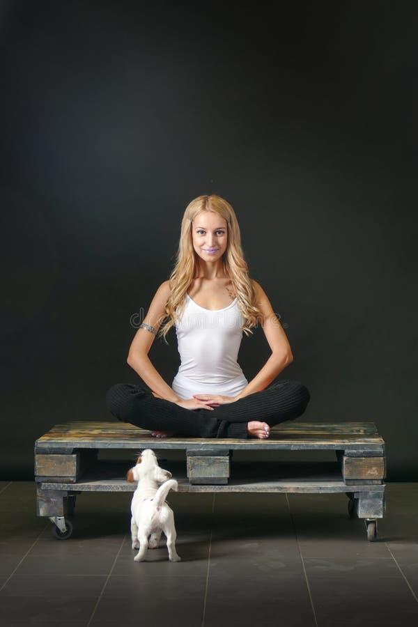 Junge Frau mit Welpen in der Yogahaltung lizenzfreies stockbild
