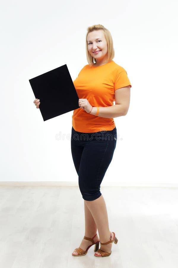 Junge Frau mit Zeichen, das sie gegen einen weißen Hintergrund hält stockfotos
