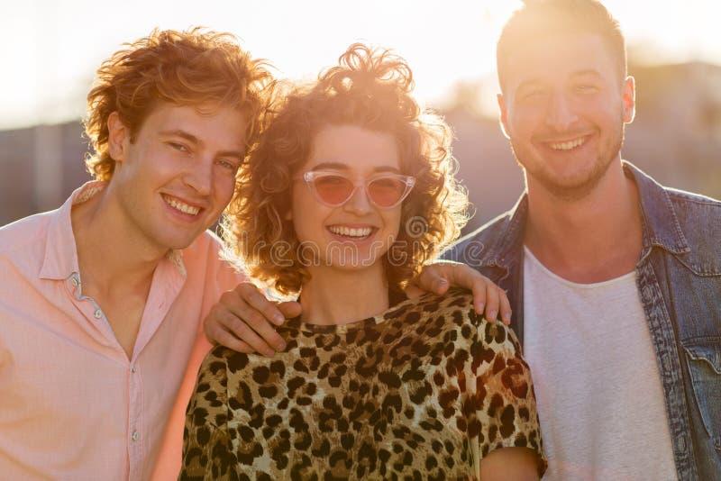 Junge Frau mit zwei männlichen Freunden stockbilder