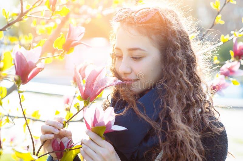 Junge Frau nahe blühendem Park des Magnolienblumen-Baums im Frühjahr am sonnigen Tag Schönes glückliches Mädchen, das Geruch in e stockfoto