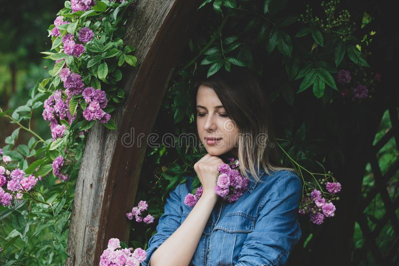 Junge Frau nahe Busch von purpurroten Blumen in einem Garten stockbilder