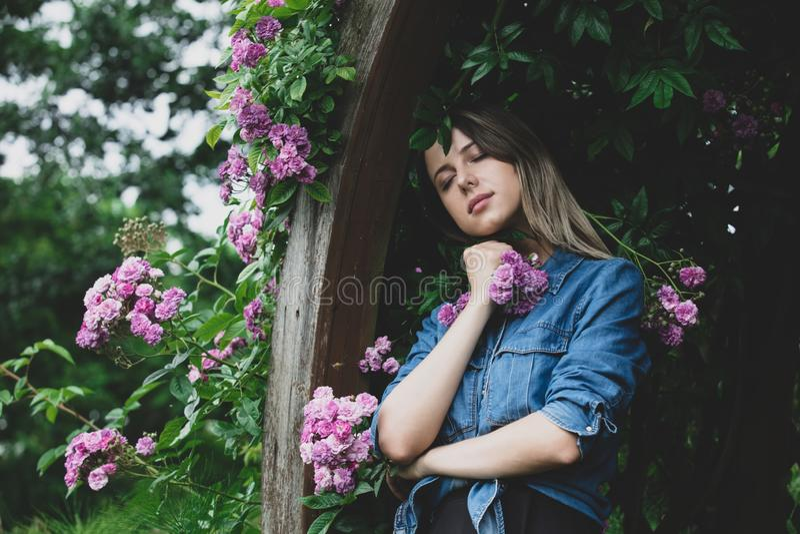 Junge Frau nahe Busch von purpurroten Blumen in einem Garten stockfotografie