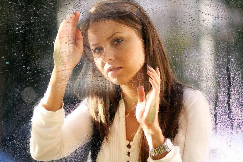 Junge Frau nahe dem Fenster nach dem Regen stockbild
