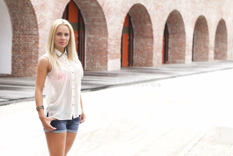 Junge Frau nahe einem Weinlesegebäude lizenzfreie stockfotos