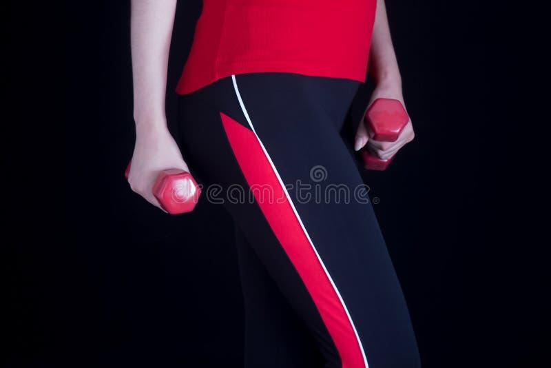 Junge Frau nimmt an Eignung in der Turnhalle teil Roter Sport Uniform und Dummköpfe Gesunder Lebensstil Richtige Nahrung und Trai stockbild