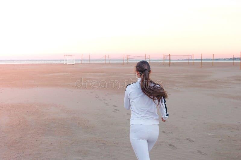 Junge Frau rüttelt auf dem Sandstrand durch das Meer bei Sonnenaufgang im Herbst, hintere Ansicht stockfotos