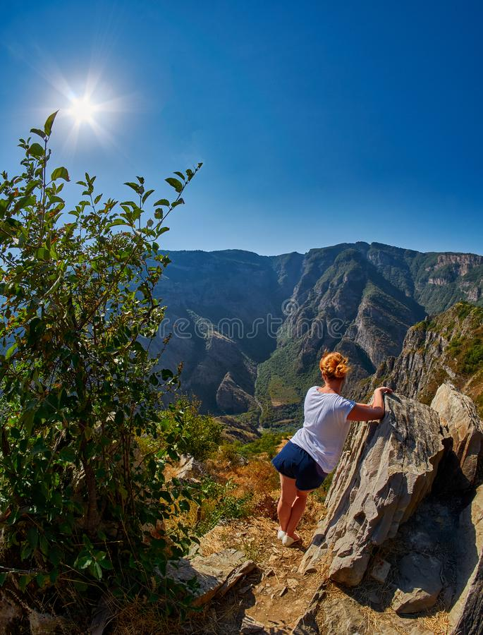 Junge Frau am Rand von Gebirgsschlucht stockfotografie