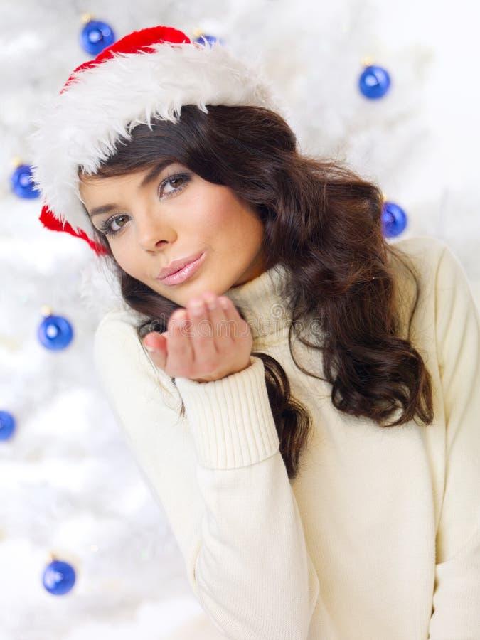 Junge Frau in Santa Hat, die einen Kuss durchbrennt stockfotos