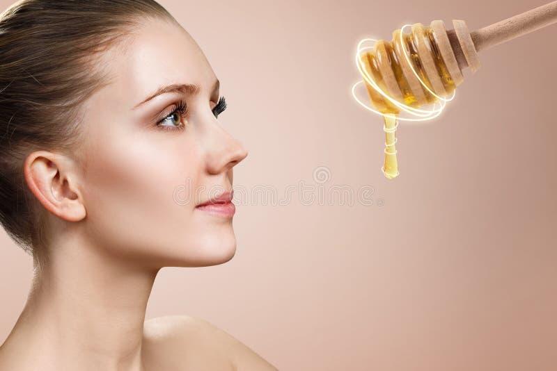 Junge Frau schaut auf Löffel mit Honig und bereitet sich für Gesichtsmaske vor lizenzfreies stockbild