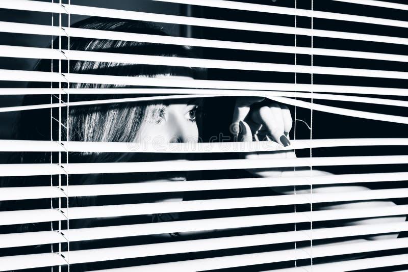 Junge Frau schaut durch den Jalousie stockbild