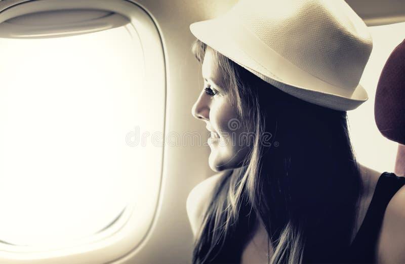 Junge Frau schaut durch ein Fenster im Flugzeug lizenzfreies stockbild