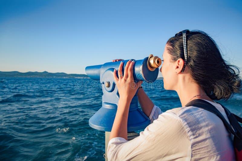Junge Frau schaut in einem Teleskop oder in den Ferngläsern durch das Meer lizenzfreie stockfotos