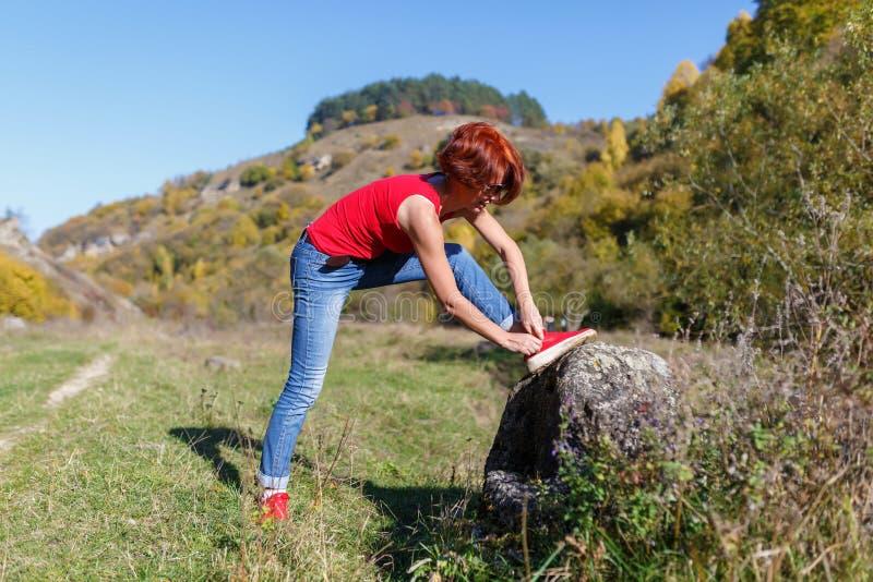 Junge Frau schnürt sich oben die rüttelnden Schuhe gegen den blauen Himmel und den Wald nach einem sonnigen Tag des Fußgängerwegs lizenzfreies stockfoto