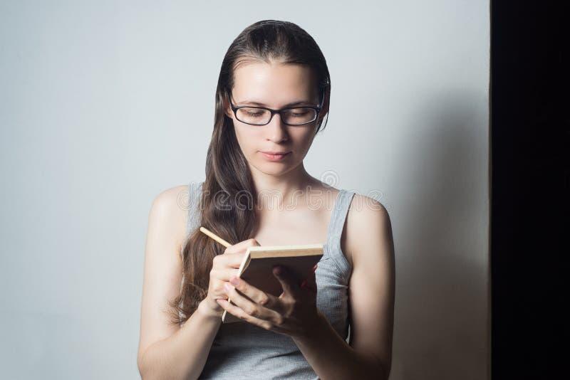 Junge Frau schreibt über Geschäft lizenzfreies stockfoto