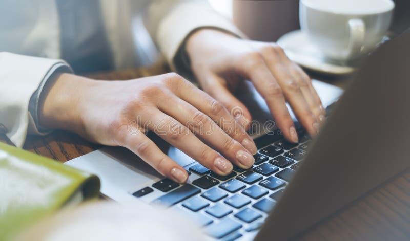 Junge Frau schreibt Händen eine Textnachricht auf Laptoptastatur mit einem leeren Monitor des leeren Bildschirms beim Haben von E lizenzfreie stockfotografie