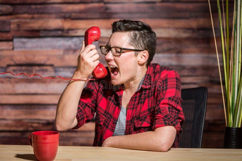 Junge Frau schreit in Telefon stockfotografie