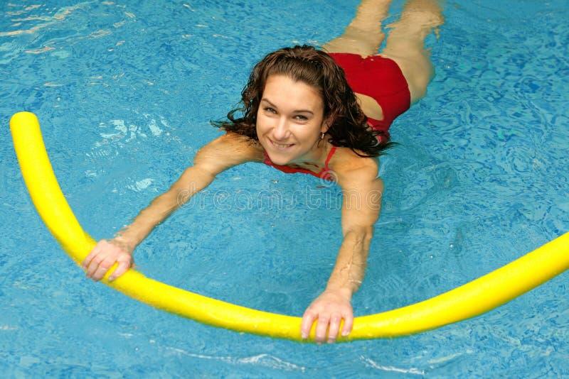 Junge Frau schwimmt mit Nudel stockfotografie