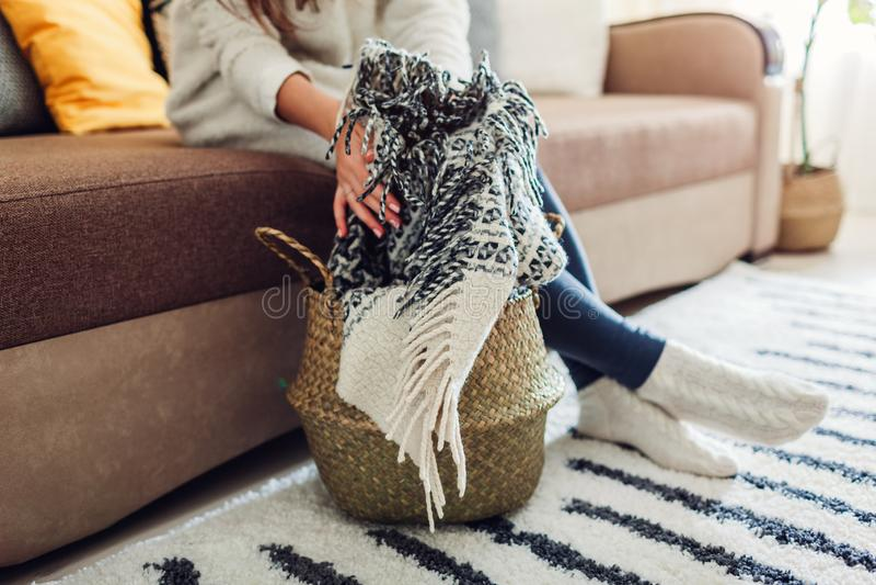 Junge Frau setzt Decke in Strohkorb ein Innendekor des Wohnzimmers lizenzfreie stockfotos